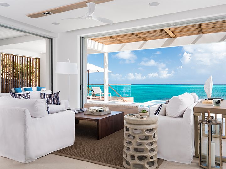 Living room opening up to a deck and an ocean view