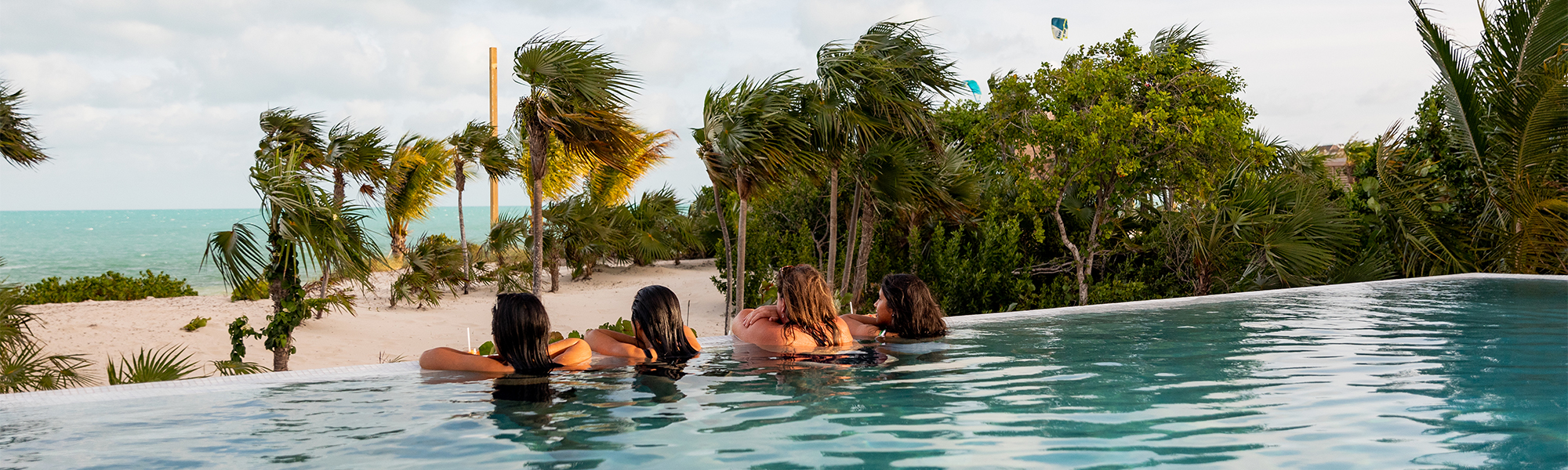 Four women in a swimming pool looking out over the ocean